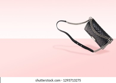 Luxury women's handbag on pink background. Steel chain and black genuine leather with texture. Free space on background