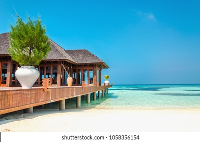 Luxury wooden house on stilts on the background of azure water and beautiful sunny sky
