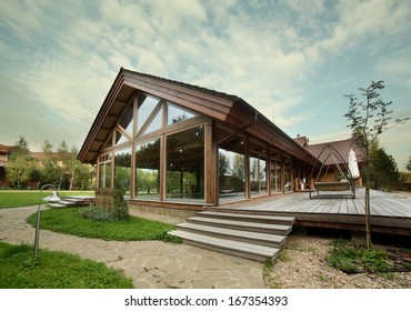 luxury wooden house with trees and swimming pool