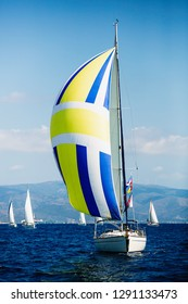 Luxury yacht with color sails at Regatta. Sailing in the wind through the waves at the Sea.