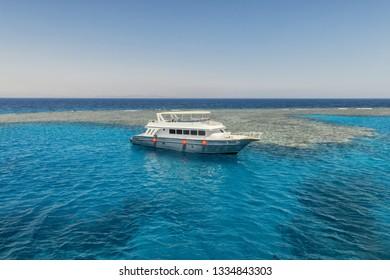 Luxury yacht docking near coral reef