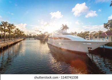 Luxury yacht moored on canal with the sun coming down at Fort Lauderdale canals. Sunset in Ft. Lauderdale, known as the Venice of America, due to its extensive and canal system. Las Olas Blvd.