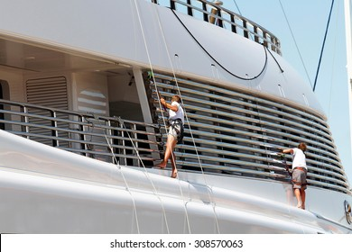 Luxury yacht moored on harbor, being cleaned