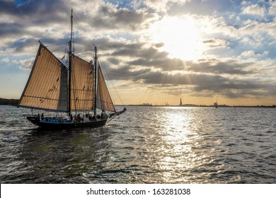 Luxury yacht sailing against sunset with Statue of Liberty in background
