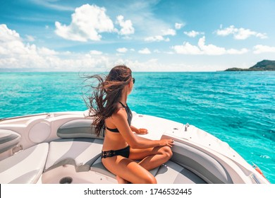 Luxury yacht woman enjoying freedom on deck in the wind relaxing on high end boat summer vacation trip upscale lifestyle of young rich people. Elegant black bikini, long hair and sun tanned body.