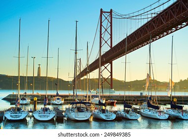 Luxury yachts under the 25 april bridge in Lisbon, Portugal