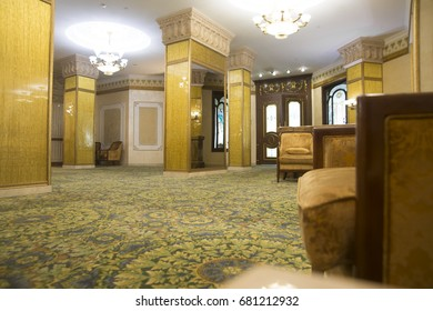 Luxury yellow golden Victorian Styled Interior background. Classical armchair, mirror table at hall room interior. Chandelier warm light and large big brown doors with glasses. Carpet on the floor