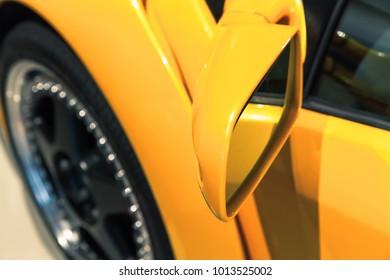 Luxury yellow sports car mirror, close up photo. Italian car design