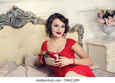 Luxury young brunette woman with a gift box in red dress sitting on a big bed.