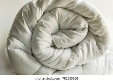 Luxury,soft,white,washable double size fiber quilt rolled on the white background.Close up taken,isolated.