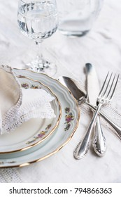 Luxyry dinner set arranged on a table with vintage cream lace tablecloth and napkins, elegant porcelain dishes, silverware and crystal glassware