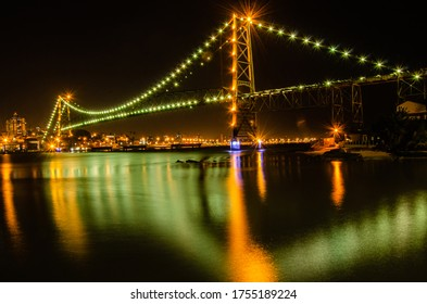 Hercílio Luz Bridge in Florianópolis and its splendid illumination reflected in the water.