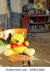 Lviv / Ukraine - 05 06 2018: plush toy sitting on chair in Yard of Lost toys, obscure touristic place with old and used plush or other children toys left behind, Lviv city, Ukraine, Central Europe