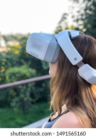 Lviv, Ukraine - 08/20/2019: Girl is wearing DGI googles to see the real time view from DJI Mavic drone. Scene is taken with personal equipment, no official occasion.