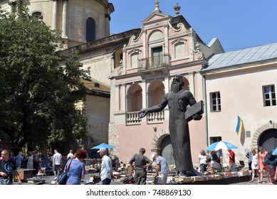LVIV - UKRAINE / 11.08.2017: The used book market in the Old Town Lviv, Ukraine and Bronze statue Ivan Fedorov
