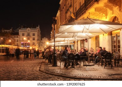 Lviv, Ukraine - April 19, 2019: Street cafe on the old streets of the night city. Lviv city in old town market square with illuminated night people  sitting at the tables in the cafe. long exposure