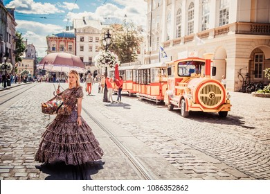 Lviv, Ukraine - April 20, 2018: Girl in retro clothes selling candies in front of sightseeing train in Lviv