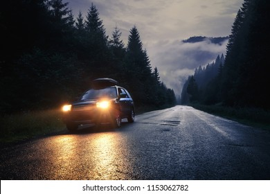 Lviv, Ukraine - August 01, 2018: Car with headlights on at night road in mountains. Travel background.