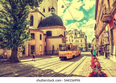 Lviv, Ukraine - August 15, 2016: Tram is in the historic center of Lviv on the corner of Market Square near Latin Cathedral. Vintage toned