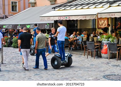Lviv, Ukraine, August 2016 - tourists walk along the old square of the city. The young man rides an electric scooter. Summer day