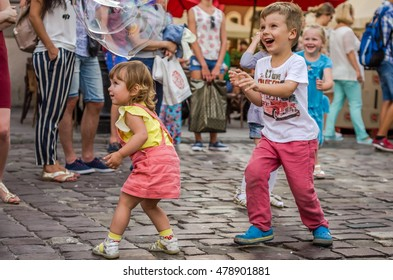 LVIV, UKRAINE - AUGUST 2016: Young children catching soap bubbles in the city, playing, joyful and radiating positive emotions, happy children