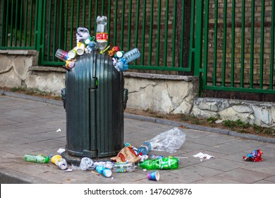 Lviv, Ukraine, August 2019. Crowded city. Overflowing garbage container near tourist attractions. Tourists go home concept.