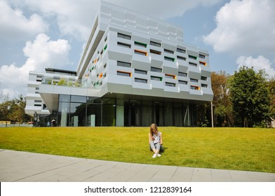 LVIV, UKRAINE - AUGUST  25, 2018 : Beautiful hipster girl is standing near the modern architecture building. Stylish business woman walking near the fashionable lines, glass and windows.