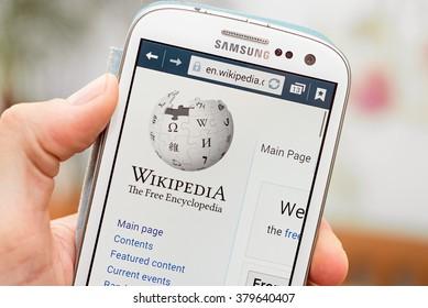 LVIV, UKRAINE - Feb 16, 2016: Hand holding white Samsung Smart Phone with Wikipedia main page screen
