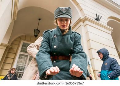 Lviv, Ukraine - February 02, 2020: Military historical reconstruction The November revolution . Sagittarius girl trying to warm hands   Lviv, Ukraine.