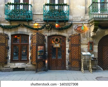 LVIV, UKRAINE - FEBRUARY 08: Beautiful restaurant exterior with antique massive wooden doors and windows with a Christmas wreath on the door in the center of Lviv on February 08, 2019 in Lviv, Ukraine