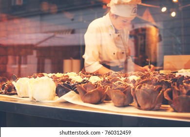 LVIV, UKRAINE - February 2015: Chocolate workshop in Ukrainian city Lviv (Lvov), view through the shop window, woman producing chocolate roses, Lviv, Ukraine. Photo with color filter added