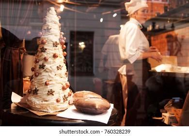 LVIV, UKRAINE - February 2015: Chocolate workshop in Lviv (Lvov), view through the shop window, woman producing chocolate sweets, chocolate Christmas tree in the shop window in Lviv, Ukraine