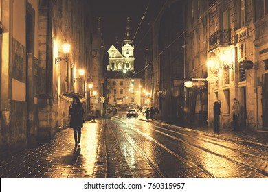 LVIV, UKRAINE - February 2015: Night view of Lviv city, city lights, shining tram rails, Lviv, Ukraine. Photo with green filter added.