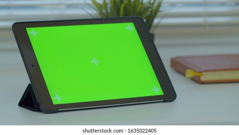 LVIV, UKRAINE - JANUARY 27, 2020: Black tabletPC on a desk with green screen and book. Close up 4k footage.