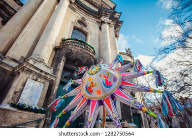 "Lviv, Ukraine - January 8, 2019: Celebration of  Orthodox Christmas in Lviv. Festival ""The flash of Christmas star"". Parade of Christmas stars. Christmas star on Dominican church background."
