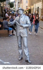 LVIV, UKRAINE - JULY 05, 2018 : Living silver statue is the entertainment for the tourists on the street in city center Lviv, Ukraine