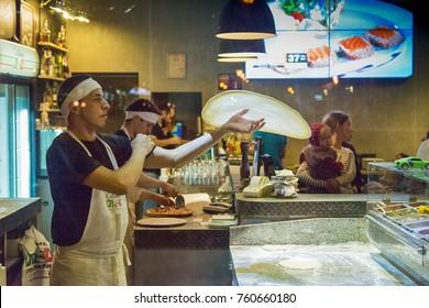 Lviv, Ukraine - July 12, 2014:  Pizzaillo in a pizzeria in the city center prepares a pizza for visitors Lviv., Ukraine.