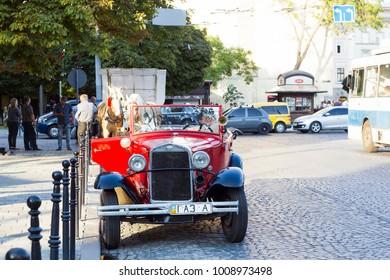 Lviv, Ukraine - July 22, 2017: Old retro Soviet red car GAZ 1936 stands on road, front view. Vintage car cabriolet on city street, summer sunny light day