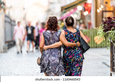 Lviv, Ukraine - July 30, 2018: Two Slavic Eastern European Ukrainian women walking back with arms around each other hugging holding in historic Ukrainian Polish city in old town