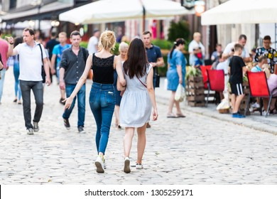Lviv, Ukraine - July 30, 2018: Historic Ukrainian Polish Lvov city during day with two girls friends holding hands walking by outdoor cafe restaurant buildings on cobblestone street in old town