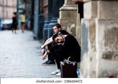 Lviv, Ukraine - July 30, 2018: Ukrainian city in old town market square with goth woman sad girl sitting on sidewalk in black clothes