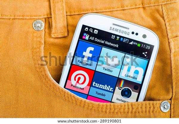 LVIV, UKRAINE - Jun 21, 2015: White Samsung Smart Phone with   social media applications  on screen in the pocket of orange jeans