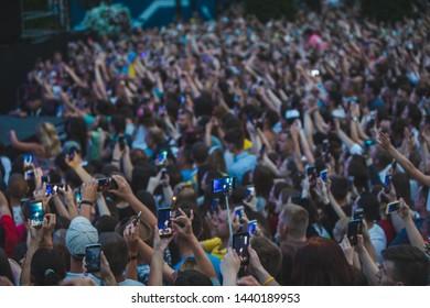 LVIV, UKRAINE - June 18, 2019: people shooting on phones rock concert near scene