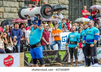 LVIV, UKRAINE - JUNE 2016: Strong athlete bodybuilder inflated with a beautiful body to lift heavy barbell on the street