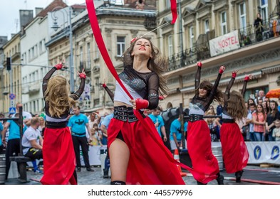 LVIV, UKRAINE - JUNE 2016: Young charming sexy girls perform a dance with her on the street in front of the audience in the red, white, black suits dresses