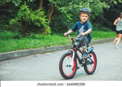 Lviv, Ukraine - June 23, 2019: little boy riding on bicycle in helmet