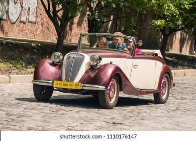 Lviv, Ukraine - June 3, 2018:Old retro car Fiat 508 C with its owner and an unknown passenger taking participation in race Leopolis grand prix 2018, Ukraine.