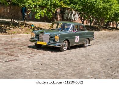 Lviv, Ukraine - June 3, 2018:Old retro car Mercedes Benz 220se (1963) with its owner and an unknown passenger taking participation in race Leopolis grand prix 2018, Ukraine.