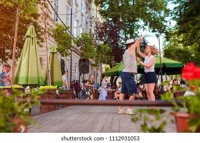 Lviv, Ukraine - June 9, 2018. People dancing salsa and bachata in outdoor cafe in Lviv