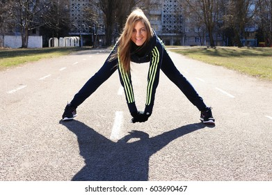 Lviv, Ukraine - March 15, 2017:  Young sportswoman stretching and warming up in Adidas and Nike sportswear. Exercise outdoors on a big soccer field.